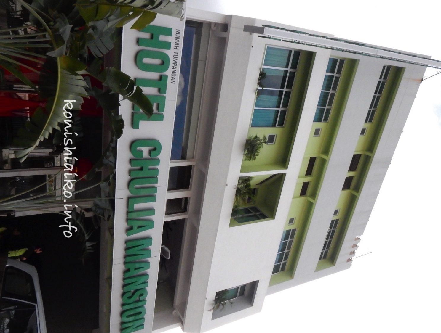 白い4階建ての建物に緑色のロゴが目印