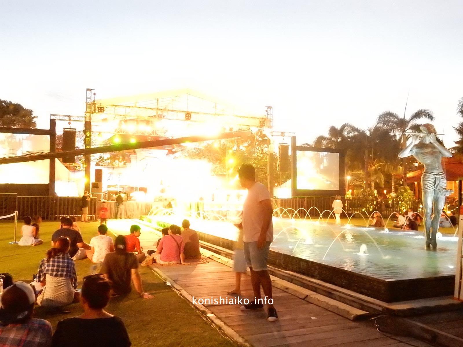 中央ステージを囲んで芝生に座る観客