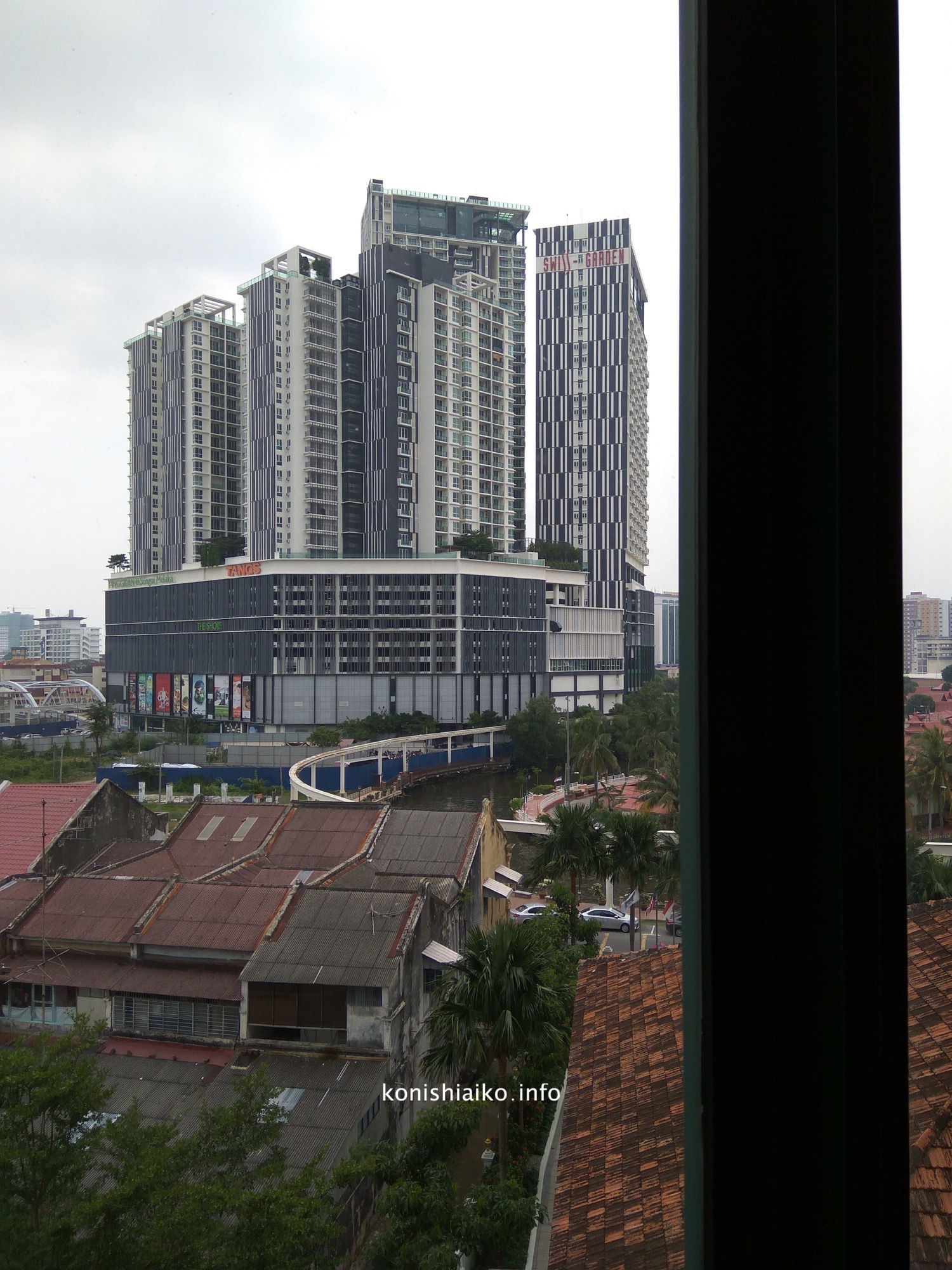 窓からの眺め。高層ビルとマラッカ川が少し見える